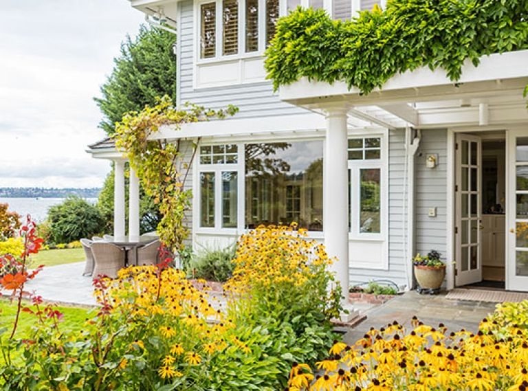 The home's entrance, contrary to most lakeside homes, faces the water, embraced by a golden-hued garden.
