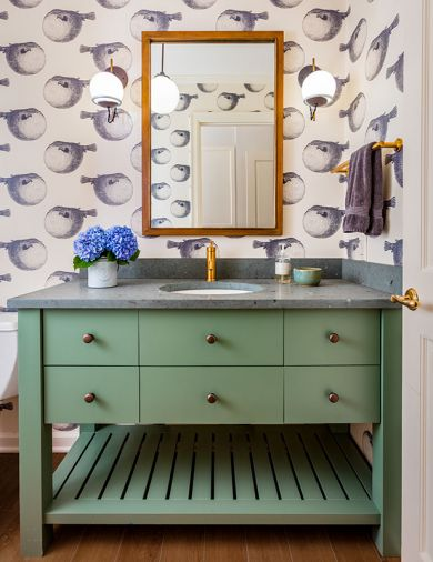 Schoolhouse Electric sconces feature decorative electrical cords and brass rods. Kohler Purist fixtures tie back to original brass door hardware. Abnormals Anonymous wallpaper; Jura Green Limestone countertop. Ann Sacks tile floor resembles wood