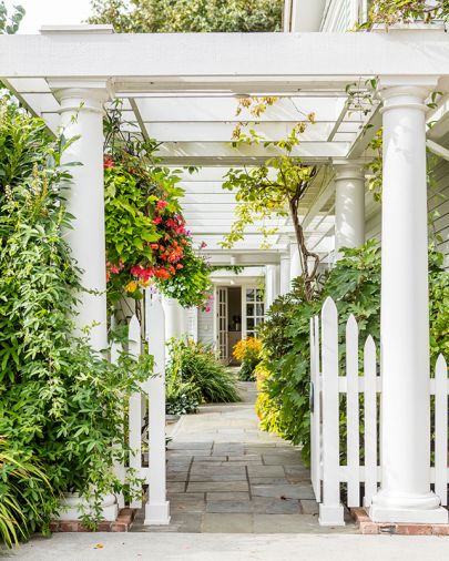Gated white entrance crowned by soaring columns mark alleyway to both kitchen ahead and formal entry at right.