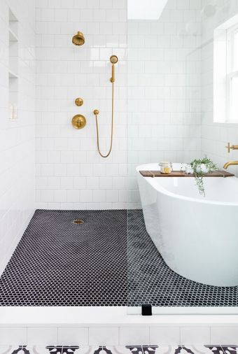 Black hex floor tiles add dramatic contrast to serene corner of master bath. Kohler Purist matte brass tub filler and fixtures echo kitchen sink hardware. Luxurious 70' Signature Hardware tub stands away from wall for easy cleaning.
