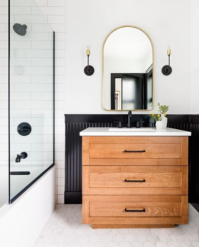 Delta Trinsic fixtures in Matte Black and School House Electric vanity sconces echo the black beadboard encircling guest bath, adding contrast against white porcelain tile floor and subway shower walls. Vanity countertop was installed by Venetian Stone Works.