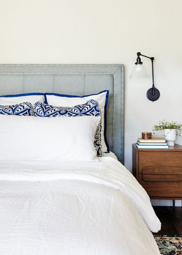 Serenity reigns in master bedroom: soft blue tufted headboard plays against geometric and blue trimmed pillows grounded by a floral bedside Joybird rug.