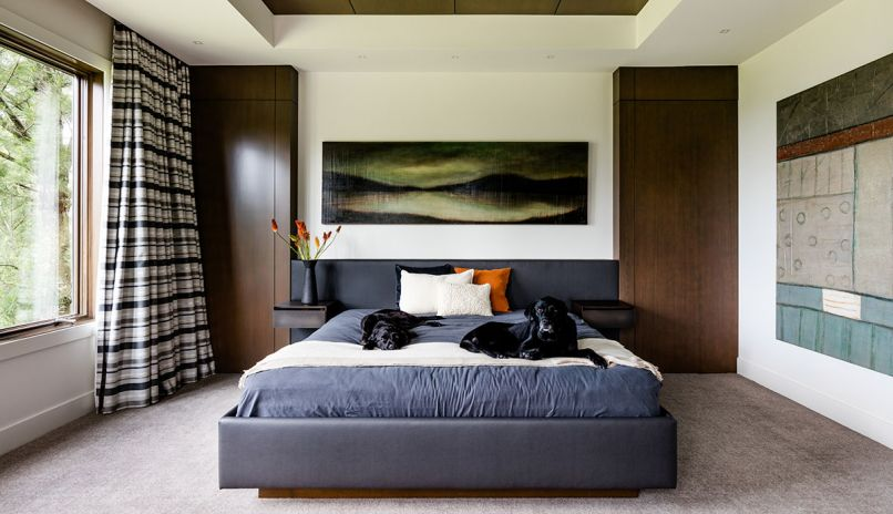 A custom headboard and bed designed to fit between the faux cabinet turned doorway at right and cabinet at left is large enough for the family's beloved black labs as well.