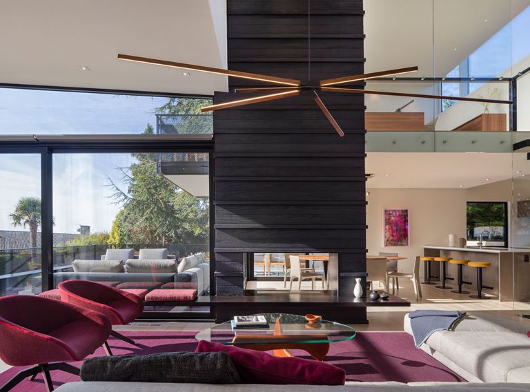 Elizabeth Stretch of Stretch Design chose vital colors to enliven the living space: burgundy rug; fuchsia furnishings pop against Shou Sugi Ban fireplace.
