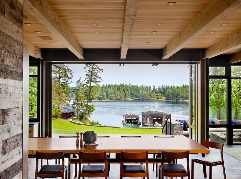 The new home, built to fit the vernacular of the historic compound, is situated on a knoll above great lawn looking toward Salish Sea through Quantum aluminum clad lift and slide doors. Custom dining table with stackable DWR profile chairs.
