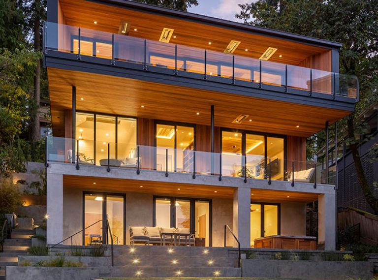 Architects teamed with Riverland Homes to replace an oft-remodeled 1930s home with modern Pacific Northwest design with unobstructed views of Oswego Lake. The team dug into steep hillside to accommodate stacked design. Truncated patio was replaced by a multi-layered landscape by Laura Canfield.