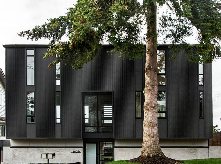 The home's corrugated metal exterior creates its architectural splendor. Window above entry features perforated metal screen reiterating interior staircase design. Entry walkway adds unexpected diagonal angle to save existing tree's roots. Evergreen tree provides year-round privacy.