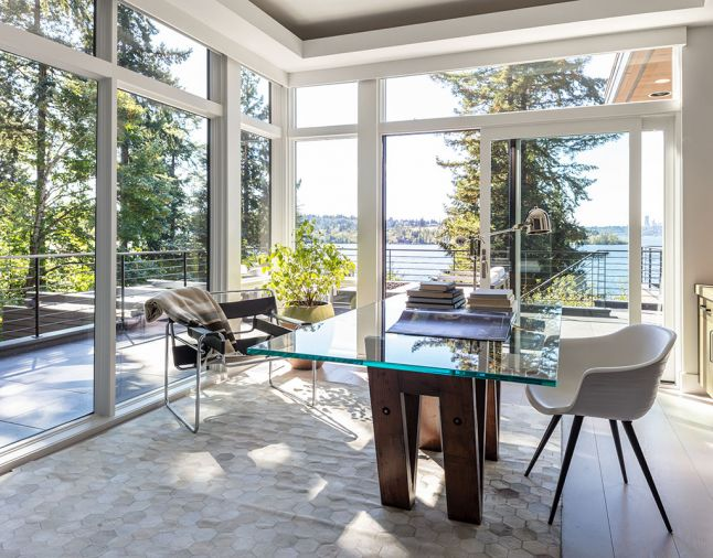 "Moon captures forest and lake views from corner home office across wraparound terraces with custom steel railings, firepit, seating and staircase down to newly landscaped yard and reconfigured pool. Restoration Hardware 72' reclaimed V-form wood and glass dining table turned desk reminded homeowner of his alma mater ""UW."" Ivory Hexa Hide rug and polished nickel Arc task floor lamp also by RH. Rug design repeats a ""hive"" theme found throughout the home. Soffit lighting when dimmed makes night-time view of lake sparkle."