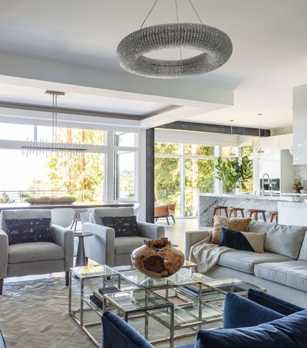 RH Crystal Halo chandelier brightens RH Keane stainless steel and glass square coffee table below. Moon reveals blackened steel moment structural frame separating kitchen from formal dining area. Box beamed dining room ceiling element continues the visual delineation.