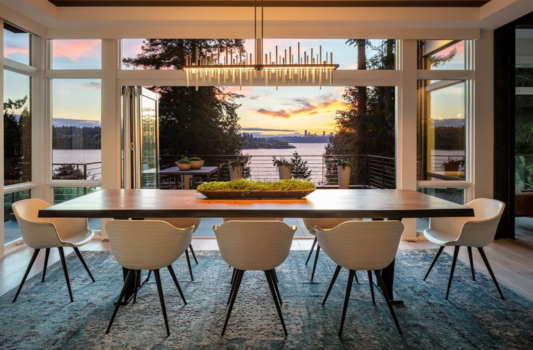 Sentient handcrafted live edge dining table from Brooklyn, New York, art studio glows beneath Cityscape Hubbardton Forge chandelier reiterating Seattle skyline beyond. Sierra Pacific accordion door.