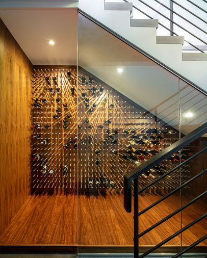aneled glassed-in wine cellar nestles beneath entry staircase, with raised walnut floor and imported pegs.
