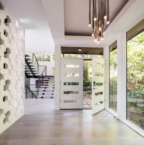 Modular Arts blocks and tiles entry wall echoes home's hive theme as does the five-glass-slotted custom entry doors. RH Aquitaine entry chandelier highlighted within box beam ceiling.