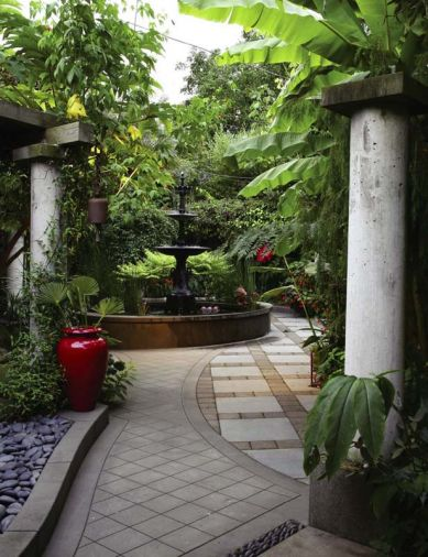 A three-story cast iron fountain is, in many ways, the garden's centerpiece. Cast concrete, such as the fountain's base and the tall columns, are one of the couple's favorite materials. Hardy banana trees and other tropical plants overlook the area and provide shade and shelter.