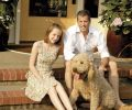 Craig Hartzman, daughter Emmarose, and Golden-doodle Samson on their sunny front porch.