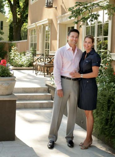 Tom and Lisa Brenneke stand alongside the back of their entirely remodeled 1909 Italian villa on a beautiful summer's day. Adjustable Lutron lighting systems set the scene at night.