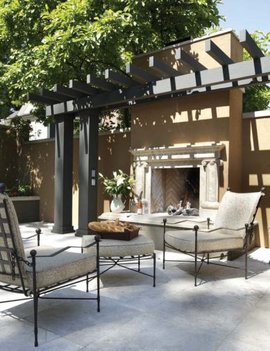 The outdoor gas fireplace is handsomely offset by a dark espresso stained arbor that reiterates the espresso colored stucco from the nearby pool.