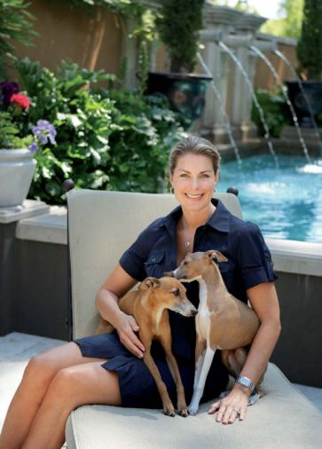 "Lisa sits at right with her beloved Italian greyhounds at the foot of the pool. ""I love the sound of the water spilling from the Cannons,"" says Lisa, of the hot water that tumbles into the 4.5' deep pool all summer long."