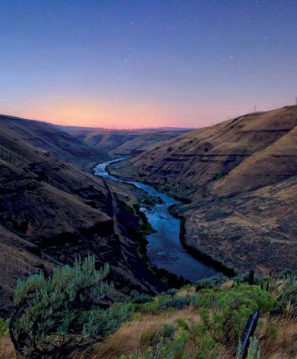 The rugged beauty of lower Deschutes River looking north across the Columbia River toward the distant windmills in Goldendale, Washington.