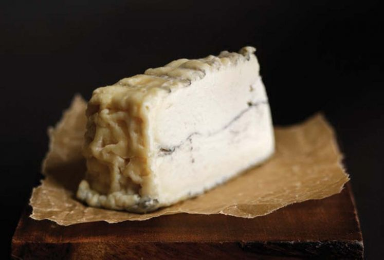 "<strong>Dutchman's Flat from Juniper Grove Farm</strong> is a mold-ripened chèvre in a 8"" by 2"" wheel. Its very delicate wrinkly rind covers a creamy interior and has an ashed exterior and center. It was named after the snow covered plain below Mt. Bachelor. Our wine pairing pick is a Buty White 2010 Columbia Valley."