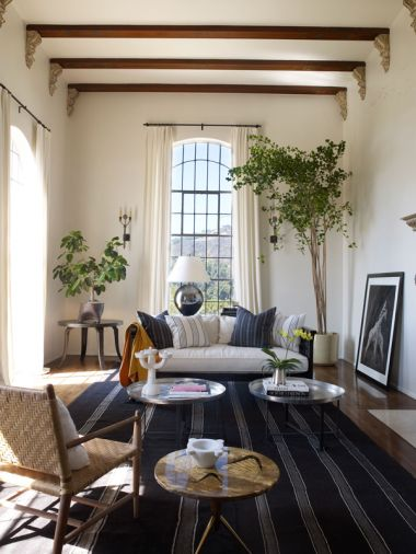 Martyn Lawrence Bullard's historic Hollywood villa for actress Ellen Pompeo and Chris Ivery. The living room ceiling soars to eighteen feet, with impressive metal framed windows. A vintage Afghan rug from Amadi Carpets fills the floor, while Moroccan tea tables from Caravane Chambre 19 in Paris mix well with a 1950s Osvaldo Borsani lacquered vellum-topped side table.