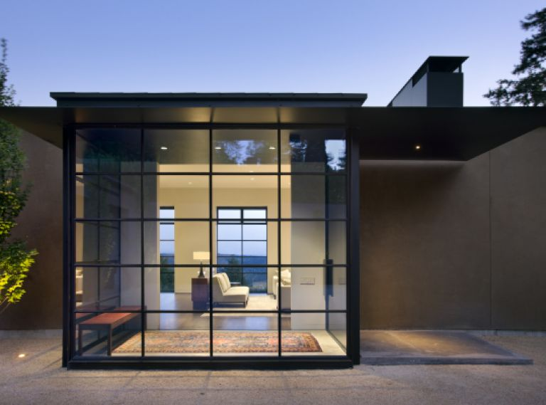 The formal entry sits outside of the private geometry of the house and within the courtyard. Using the same ceiling and floor surfaces on the outside and inside creates a place to welcome guests while still clearly separating the public space from the private home. Steel windows and stucco are elements used throughout the design.