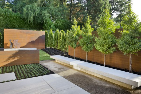 Panels, concrete benches, geometric planting beds and trees with a strong linear line were used to tie the house to the outdoors in a transitional garden space designed by landscape architect Andrea Cochran.