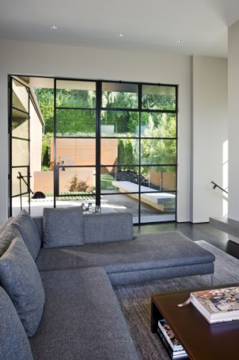 The rectangular configuration of the steel-framed windows is reinforced by the shapes of the hardscape viewed through the panes.