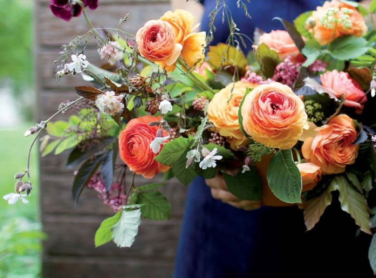 Eye-catching orange and chocolate tones highlight a bouquet of copper beech, black elderberry, ranunculus, sweet peas, grasses, mallow, nine bark, bronze fennel and snowberry foliage.