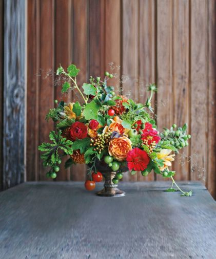 Garden of Eden: Edibles can add spice, texture and pops of unexpected color to arrangements. Shown is a mixture of scented geraniums, viburnum berries, nasturtiums, tomatoes, garden roses, baby apples, berries, crabapples, and grasses.