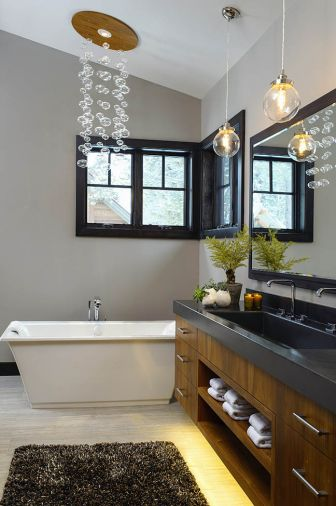'The homeowner wanted a hanging bubble light fixture over the bath tub,' the designer explained. 'The electrical code prevents you from hanging a fixture over a tub. I designed the faux - fixture to look like the bubble light. It is actually a recessed ceiling light with a teak trim piece with hanging globes.'