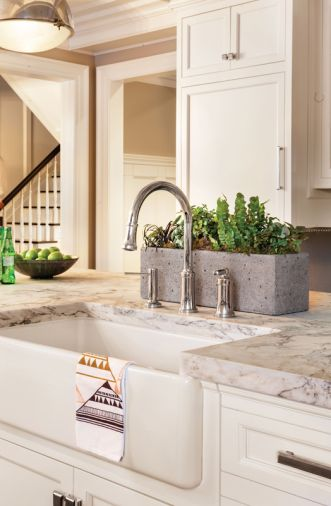 A handy 36' farmhouse sink is paired with a Kallista 'Quincy' Nickel faucet for food prep.