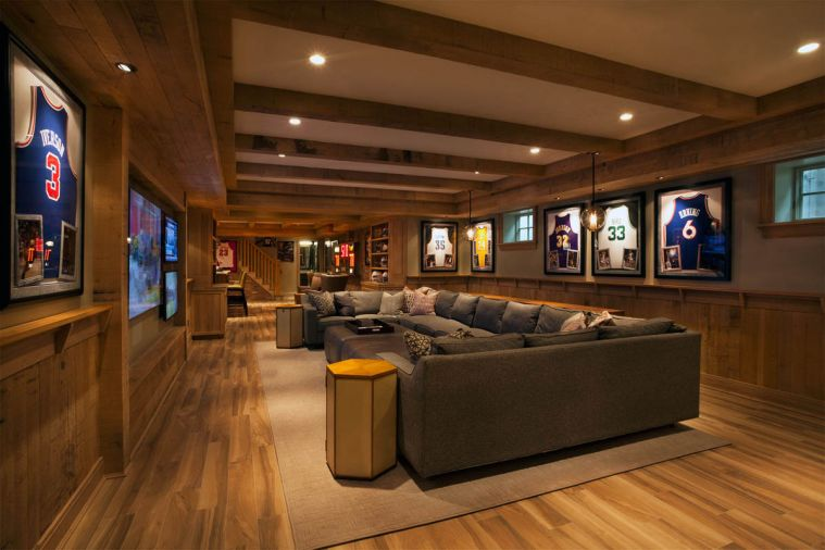 Rough sawn oak walls feature basketball memorabilia in the basement. Spacious seating, and multiple TV screens promote casual entertaining. Highly resistant porcelain plank flooring resembles wood.