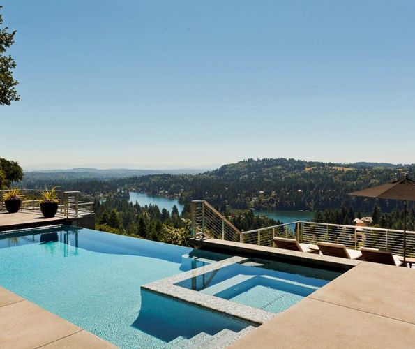 The infinity pool by Blue Mountain Pools, which includes a spa, overlooks the extraordinary view. Landscape design by Michael Schultz references nature's greenery seen throughout all four seasons. A few steps down from the pool, sunbathing on a quartet of chaise lounges can be enjoyed, once again facing the beautiful scenery.