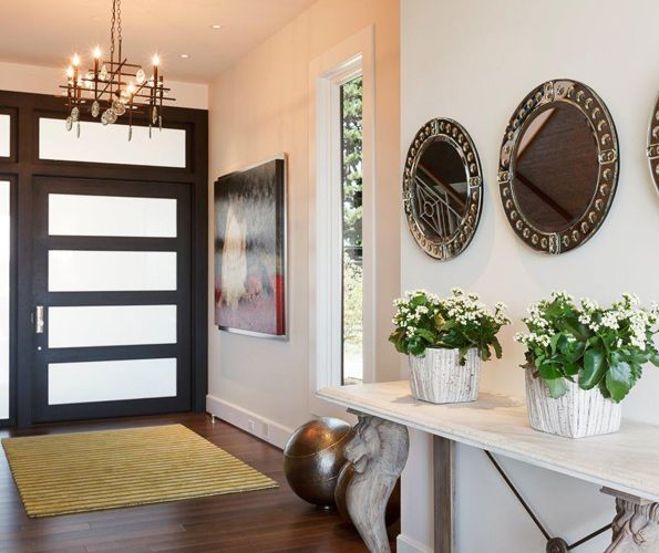 The Portland Millwork custom made ebony stained front door mixes with a citrine Kravet entry rug.