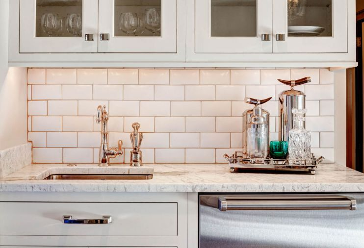 A sink, dishwasher drawers and cabinetry for glassware provide a second prep and bar area near the living areas.