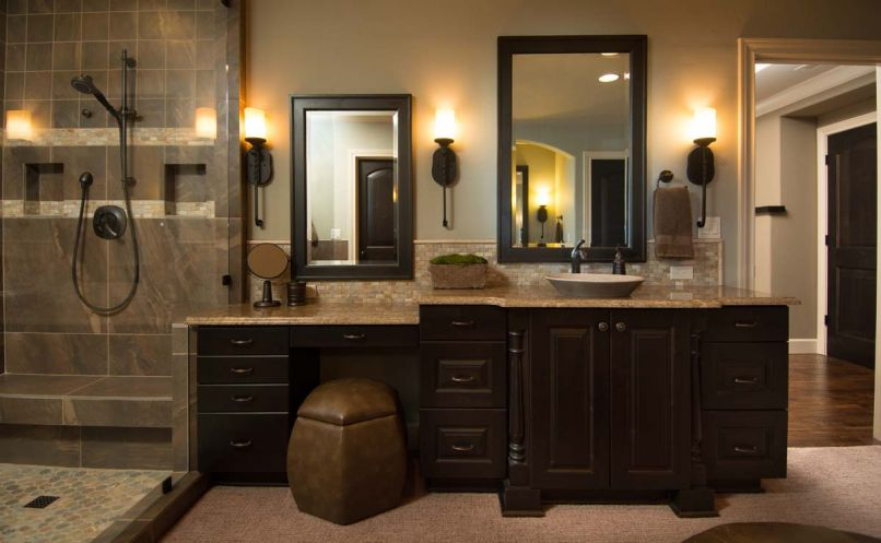 In the bathroom, cabinet design and granite counters are repeated from downstairs and Kohler sinks are mated with Delta faucets. To provide plushness under foot, the homeowner requested the floor be carpeted.