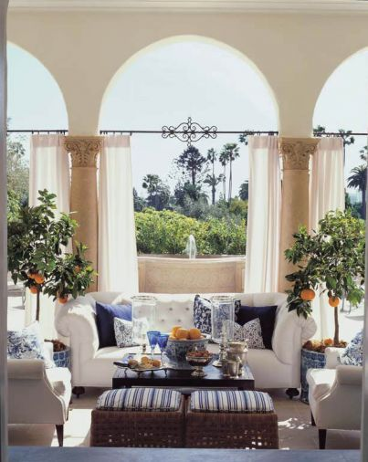 Iron rods were custom-made to hang atmospheric curtains on the back loggia of the Buster Keaton estate, which has English-style furniture upholstered in white canvas and blue-and-white Ralph Lauren fabrics.
