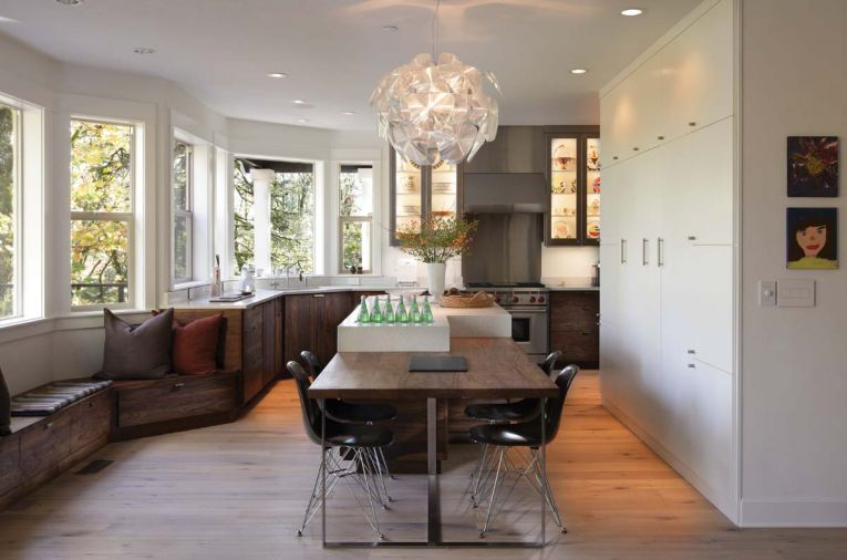 In this Portland kitchen designed by Barbara Sumner, the island's horizontal bookmatched solid Western walnut from Crosscut Hardwood was used to ground the outer perimeter of the room. Sumner used walnut, quartz and stainless to unify the 16-foot-long island and seating area. Stainless steel legs were manufactured by Hanset Stainless, which also clad the cabinetry.
