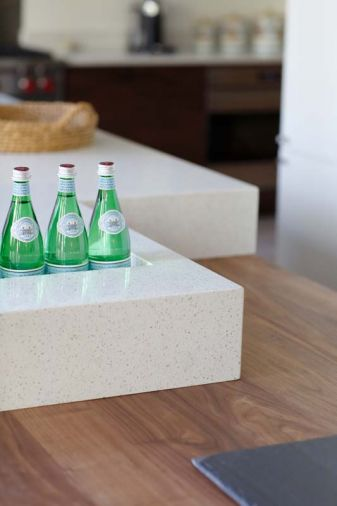 On the island, the quartz work surface was sculpted to provide a self-draining ice bucket or a planter box; when not needed the opening can be seamlessly covered with a matching quartz slab. Quartz has become increasingly popular among designers and homeowners because of its easy maintenance, durability, and stain and heat resistance. Resins bind natural quartz and pigments to create an endless array of colors in several finishes that can then be molded or sculpted to suit the specific purpose.