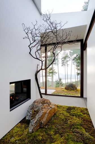 Budget-friendly, green building solutions include a double-sided steel manufactured fireplace found on Craigslist and framed in black-painted glass that reflects the outdoors. Live moss, rock and a dried Madrona branch greet guests, maintaining visual flow of natural vegetation from outdoors in.