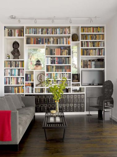 The library provides an intimate space in which to read or watch TV. A portrait chair by the owner's stepson immortalizes her late husband. Like the dining and living rooms, the library opens to the walled back yard and pool.