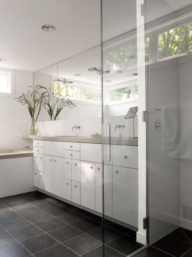 A mirror running the width of the wall above the sinks reflects light into the master bath.