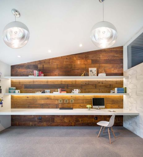 A new home office was created from a garden storage area and seamlessly adopted into the home's architectural design. Capitalizing on the rest of the structure's mid-century elements, the space features streamlined shelving with integrated lighting, a PentalQuartz desktop and locally sourced barn wood that has found a second life as wall paneling.