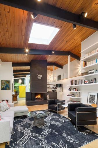 A central fireplace graphically connects the floor to the two-story ceiling and keeps the room to human proportions. The Vanillawood team painted it and the beams black to bring the home's exterior colors indoors.