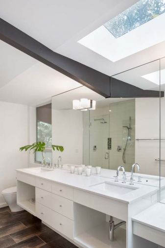 A skylight was added to visually lift the roof in the master bath. Custom vanity was treated to a durable automotive finish technique.