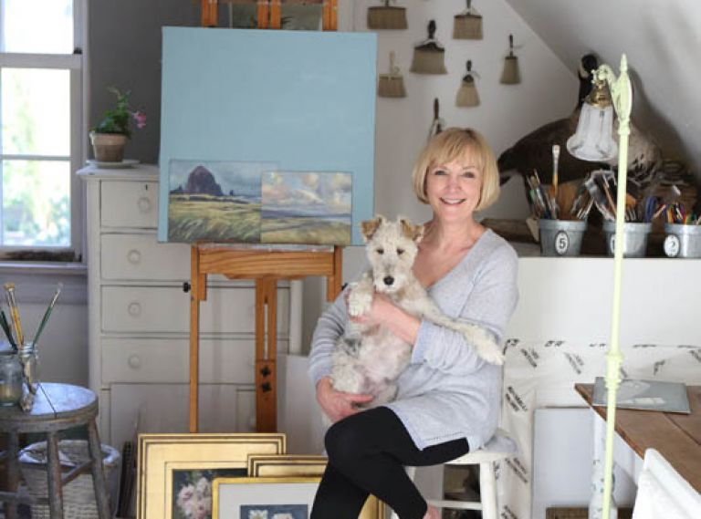 Diane in her upstairs studio with their fox terrier Lily.