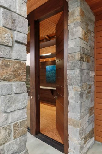 Low maintenance Oregon and Idaho natural stone frames the 10' walnut entry door from Western Pacific Building Materials, with veneer by Garis Woodworking, Inc., opened here to view the walnut screen wall and Night Water #6 painting by Leigh Li-Yun Wen.