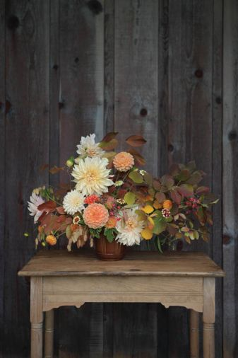 You can assemble this autumnal arrangement designed by Kailla Platt yourself by using these plants and stem count: 6 Dahlia 'Cafe au Lait,' 2 Dahlia 'Crichton Honey,' 5 Zinnia 'Persian Carpet,' 3 Cockscomb Celosia, 3 Northern Sea Oats, 3 Dahlia 'Ginger Willo,' 2 Fothergilla foliage, 2 Euonymus europaeus, 3 Heptacodium, 3 Blueberry foliage, 5 Scented Germanium foliage, 2 Viburnum plicatum.