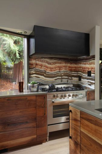 A granite backsplash ties together the tones in the kitchen with the hues seen outside. Drawers by the range provide storage for herbs and spices. Designer and homeowner Christina Tello believes in form following function, which her husband took to heart when he gave her the tree branch salt and pepper shakers.