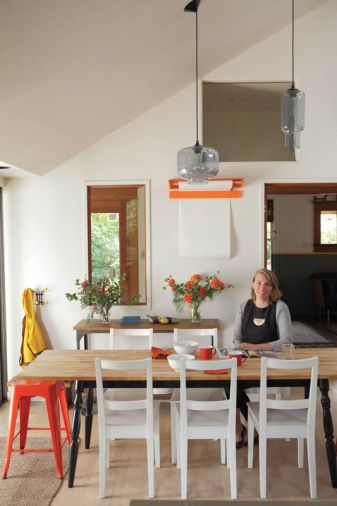 The dining area of the remodeled kitchen is so successful that the couple turned the home's formal dining room into a library. A wall-hung orange paper cutter holds a roll of paper for children's artwork or for adults' games of Pictionary. The table and chairs are from Ikea while the orange stool is from Wayfair. Often the hub of all activities, the kitchen was designed with enough open space for family and guests to congregate and socialize.